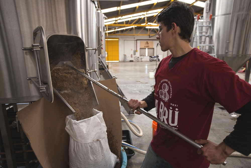 Brewmaster Ernesto Herrera Removing Steaming Spent Grain from  Cerveceria La Bru's PKW Brewhouse